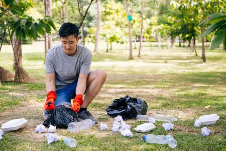 Young Asian man wearing orange gloves and collecting trash in garbage bag in the park. Save the earth and environmental concern concept Zdjęcie Seryjne