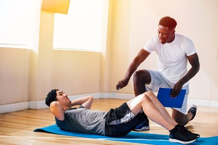 Side view of Asian man lying on floor doing abdominal exercises while African American trainer kneeling besides and teaching in fitness club