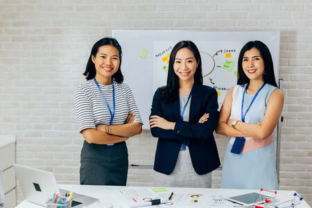 Smiling Asian young business women in casual wear standing in line with arms folded in meeting room. Row of Business men and women looking at camera