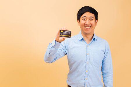 Retrato de joven asiático feliz sosteniendo una tarjeta de crédito y mostrando una sonrisa en el fondo de color beige. Oficinista de cuello azul mirando a cámara y disfrutar de las compras. Consumismo y concepto bancario