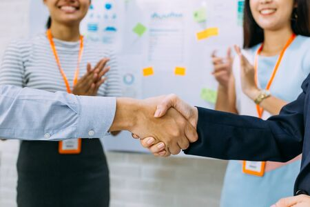 Young Asian business man and business woman giving a handshake gesture and cheering business workers clapping in background of meeting room