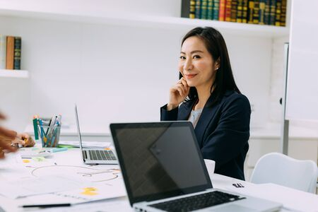 Asian mature business woman smiling and looking at camera while sitting in meeting. Smart middle age lady portrait