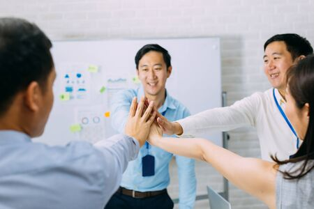 Young Asian business people gathering and putting hands together in meeting room. Business men showing unity and collaboration gesture. Stock Photo