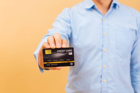 Portrait of young happy Asian man holding a credit card and showing smile in beige color background. Blue collar office worker looking at camera and enjoy shopping. Consumerism and banking concept