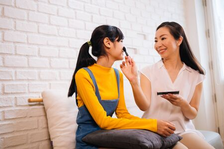 Smiling adult Asian woman using makeup brush and applying blusher on cheeks of young charming daughter while sitting together on sofa in living room