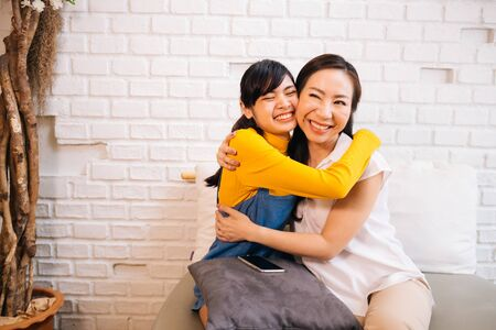 Loving smiling Asian women hugging happily while sitting together on couch at living room Archivio Fotografico - 130041034