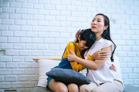 Asian mother comforting crying teenage daughter in miserable, stressed, depressed, sad state of mind. 40s Mom is hugging this adolescent teenager shoulders at indoors room.