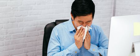 Sick male entrepreneur sneezing with napkin at office with copy space. Asian young man with allergy and disease