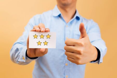 Businessman showing five yellow stars card and thumbs up in bright color background. Review, rating, ranking and evaluation concept