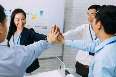 Jeunes hommes d'affaires asiatiques se réunissant et mettant les mains ensemble dans la salle de réunion. Hommes d'affaires montrant un geste d'unité et de collaboration.