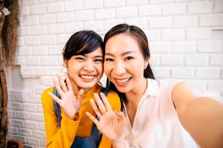 Face of smiling happy Asian teenage daughter and Asian middle-aged mother looking at mobile phone in indoor living room at home. It could be video calling or taking a selfie photo together. Stockfoto