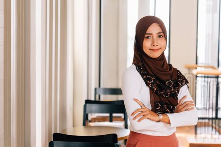 Young happy and successful South East Asian Islamic business woman with arms crossed in business corporate building setting looks at camera. She wears headscarf or hijab and modern elegant clothes Stock Photo