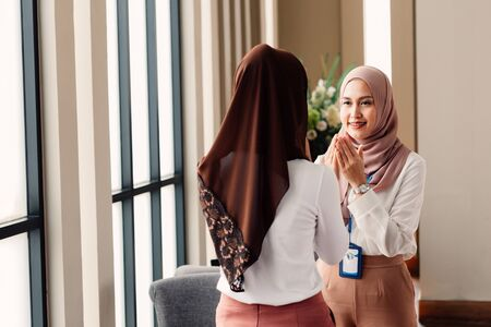 Young Asian Islamic business woman with happy smile in corporate office building greets and welcomes other muslim woman in hijab with respect.