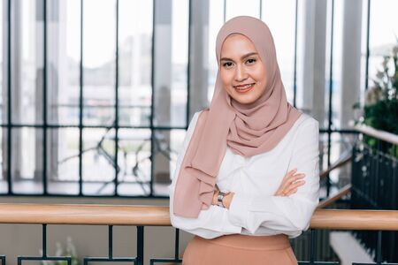 Young happy and successful South East Asian Islamic business woman with arms crossed in business corporate building setting looks at camera