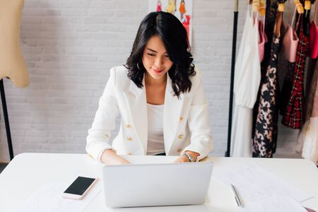 Contemporary confident Asian lady entrepreneur in stylish jacket working on laptop with garment hanger on background Stok Fotoğraf
