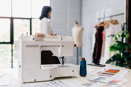 Machine à coudre blanche automatique et motifs sur table en atelier studio avec styliste floue sur fond Banque d'images