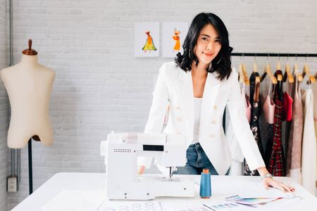 Content Asian fashion designer standing at table with sewing equipment and smiling at camera in light workshop 스톡 콘텐츠