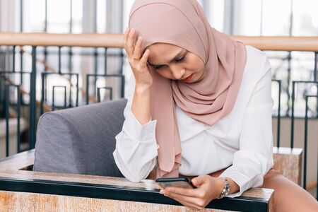 Sad Asian female in hijab touching forehead and browsing smartphone while having problem in cafe