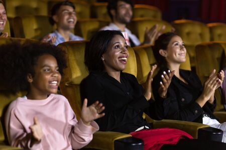 Excited black woman and girl audience smiling and clapping hands while sitting amidst people after movie in cinema