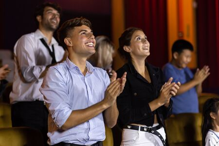 Amazed cheerful man and woman smiling and applauding while standing at seats in cinema hall after movie looking on stage