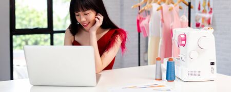 Contemporary confident Asian female entrepreneur and fashion designer in white shirt working on laptop with garment hanger on background