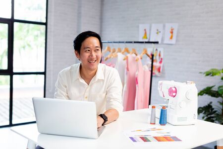 Contemporary confident Asian male entrepreneur and fashion designer in white shirt working on laptop with garment hanger on background Zdjęcie Seryjne