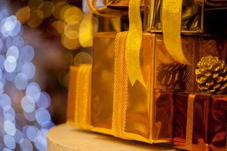 Close-up of golden gifts piled up in stack blurred in gold bokeh background - (selective focus) 스톡 콘텐츠