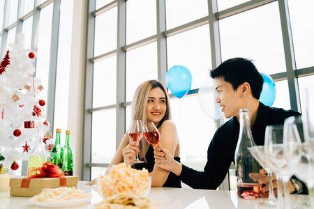Una giovane coppia asiatica adulta con in mano un bicchiere di vino celebra la festa di Natale in un condominio di lusso. Hanno snack, regali e albero di Natale sul tavolo.
