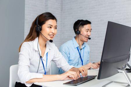Alegre hombre y mujer asiáticos en auriculares sonriendo y escribiendo en el teclado de la computadora mientras trabaja en la oficina del centro de llamadas