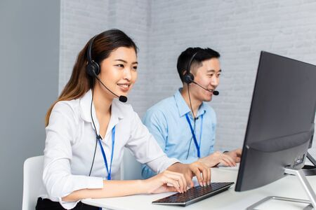 Cheerful Asian man and woman in headsets smiling and typing on computer keyboard while working in office of call center