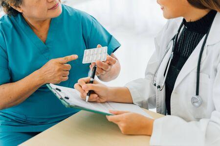 Paziente anziana che chiede prescrizione sui medicinali di una giovane dottoressa in uniforme all'ospedale