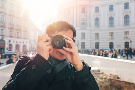 Young Asian man tourist taking photos with camera in hands near Hofburg palace in Vienna, Austria, Europe. Famous popular touristic place in Europe