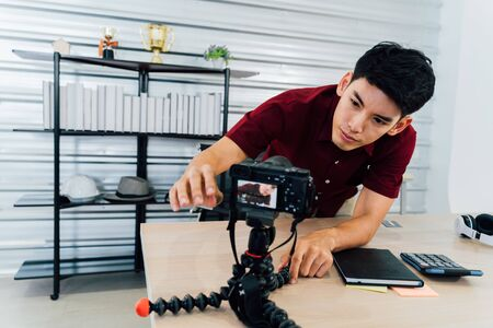Serious Asian male adjusting camera for video shooting busy hipster preparing for recording vlog at workplace