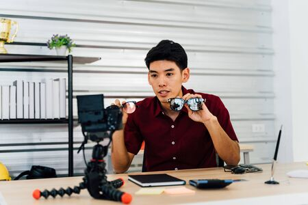 Asian man recording video using camera selling sunglasses through social media and video platform sitting at table at workplace