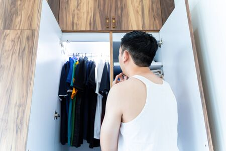 From below back view of black haired man in white shirt thinking about what to wear in front of modern cabinet