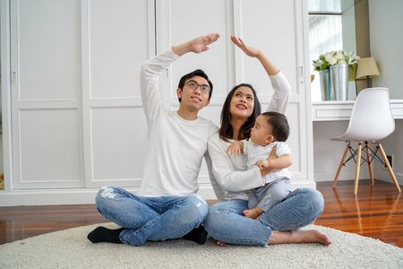 Positive young Asian married couple with infant boy looking up and making roof figure with hands while sitting on carpet in lightroom