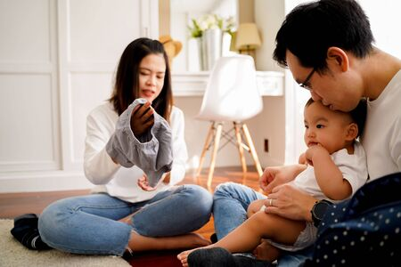 Young Asian father sitting on floor and holding infant boy while mother holding baby clothing and together taking care of son and changing diapers Stock fotó
