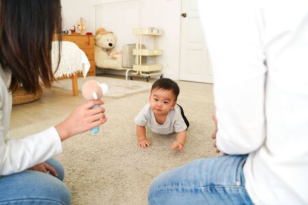 From above of Adorable Asian Infant boy looking at toy in hands of mom and crawling on carpet towards parents while family spending time together at home