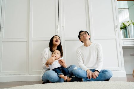 From below of positive young Asian married couple with baby boy looking up admiringly while sitting together on floor against white wardrobe in room Stock fotó