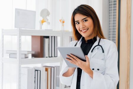 Pleased Asian female physician in white uniform smiling and looking at camera while using digital tablet in office of hospital