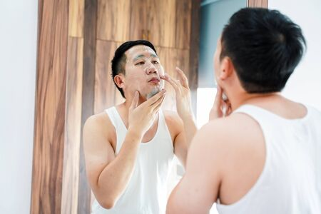 Back view of contemporary Asian man in white shirt applying skincare mask for face while looking in in mirror in bathroom Stock fotó
