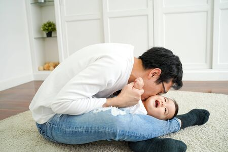 Side view of young Asian man in casual white shirt and jeans sitting on floor and hugging and kissing infant boy while playing together in living room