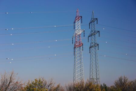Electric high voltage pole and Power pole voltage lines over the blue sky - Electricity and energy generation