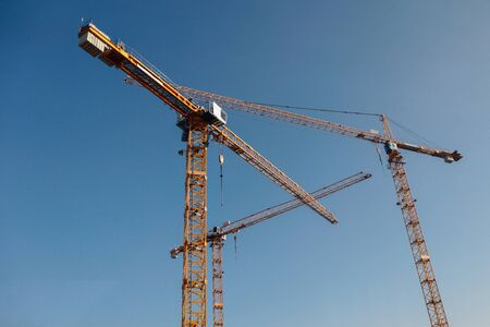 Luffing jib tower crane at large scale construction site over blue sky 写真素材
