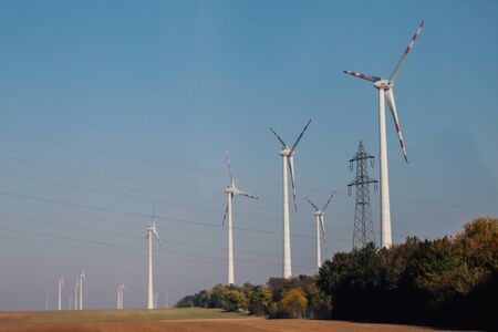 Naturally friendly wind turbines generating energy against blue sky in sunny autumn day