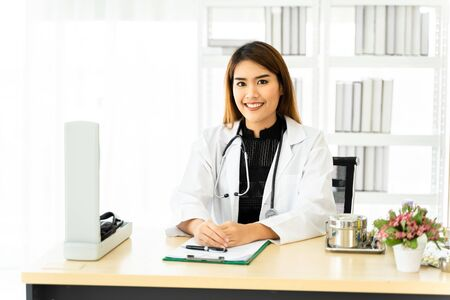 Smart young Asian female doctor in uniform smiling and looking at camera while doing paperwork at desk in office of hospital Stock fotó