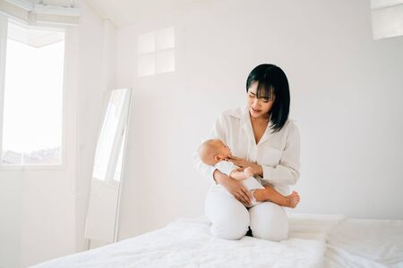 Caring Asian mother holding newborn son on hands little baby sleeping in bedroom of modern house Stok Fotoğraf - 137878383