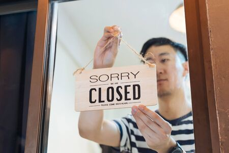 Through glass view of Asian male business owner hanging up sign with inscription closed at end of working day