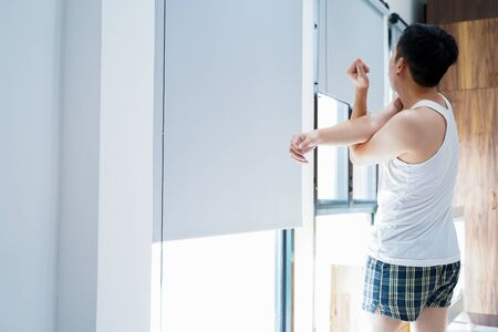 Back view of black haired male in home clothing standing and stretching arms in bedroom on sunny morning Stock fotó