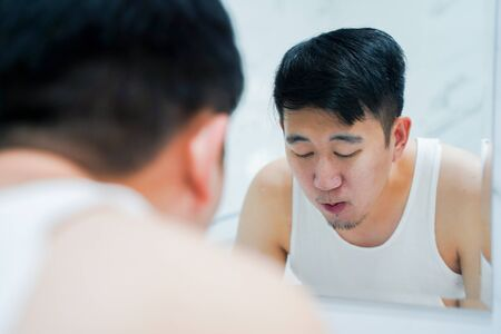 Back view of young Asian man in white shirt gargling and rinsing mouth after brushing teeth in front of mirror in bathroom